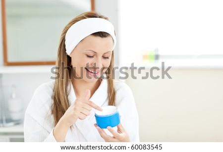 Radiant woman putting cream on her face wearing a headband in the bathroom at home - stock photo