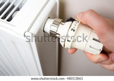 Radiator adjustment closeup. Man's hand adjusting radiator temperature. - stock photo