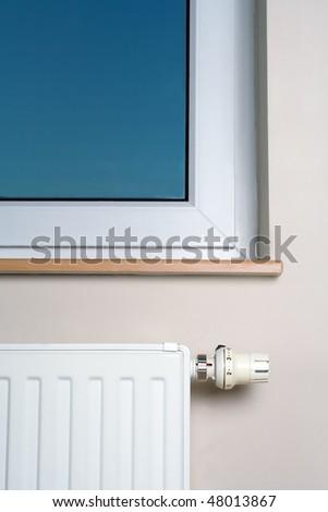 Radiator and window in home interior - stock photo