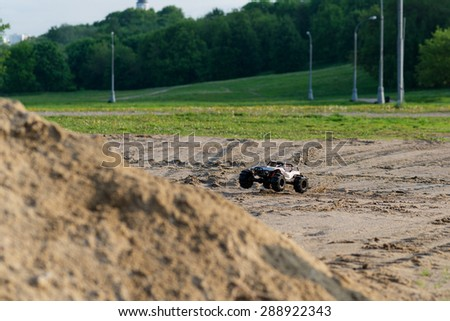radio controlled monster truck on the sandy ground in the summer park at fast speed close to a large pile of sand. soft focus and beautiful bokeh - stock photo
