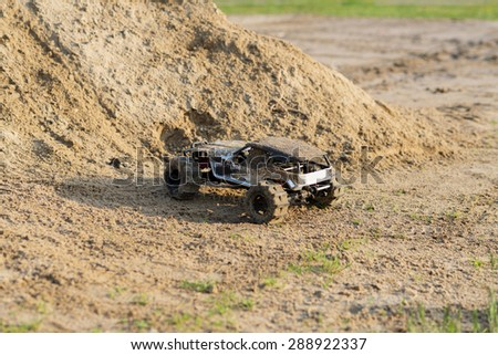 radio controlled monster truck performing a trick at high speed jumps over a large pile of sand. soft focus and beautiful bokeh - stock photo