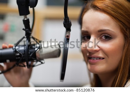 Radio host posing with a microphone - stock photo
