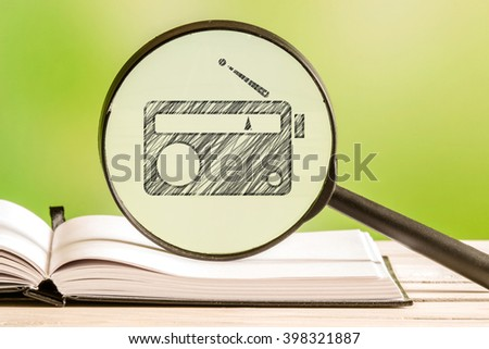 Radio information with a pencil drawing of a transistor radio in a magnifying glass - stock photo