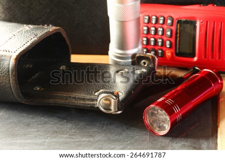Radio transmitter use in citizen band and leather holder put beside torch represent the communication technology concept . Super macro shot and intention focus at the radio leather holder. - stock photo