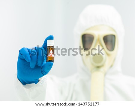 Radioactive isotope sample in a small brown bottle with a warning label held in the fingers of a laboratory scientist in full protective clothing with a mask and breathing apparatus - stock photo