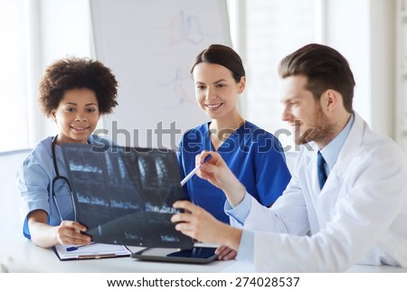 radiology, people and medicine concept - group of happy doctors looking to and discussing x-ray image at hospital - stock photo