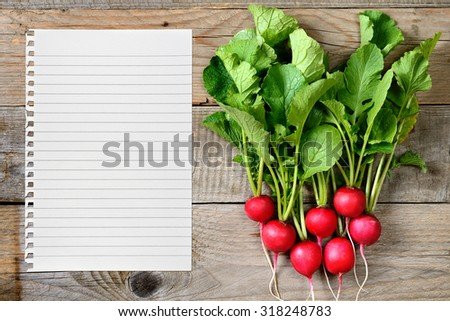 Radishes and paper for recipe on wooden background - stock photo