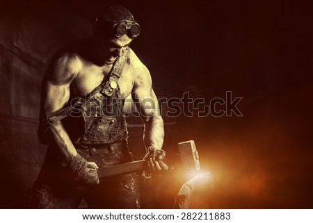 Rage muscular coal miner working with a hammer over dark grunge background. Smithy. Mining industry. Art concept. - stock photo
