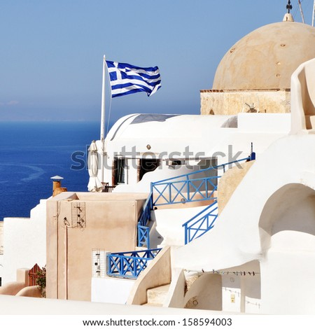 Ragged flag of Greece waving in wind vertical. Oia, Santorini, Greece - stock photo