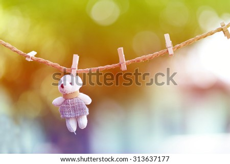 Rail clothespin and a teddy bear in the background. - stock photo