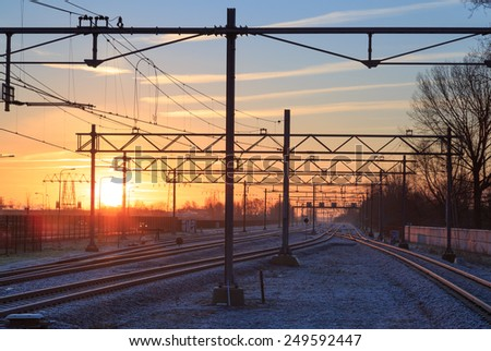 Railroad and  overhead wiring at a winter sunrise. - stock photo
