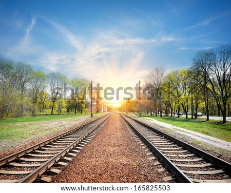 Railroad at sunrise in sunny spring day - stock photo