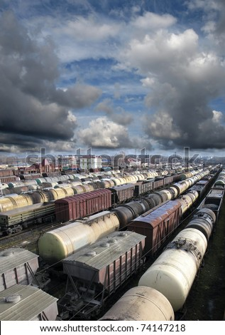 Railroad cars on a railway station. Cargo transportation. Storm clouds above train - stock photo