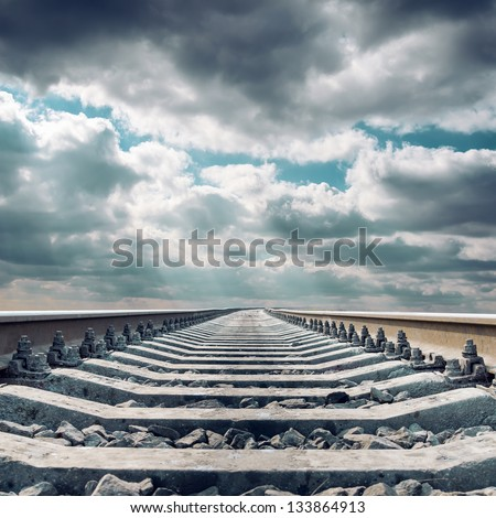 railroad close up to horizon under dramatic sky - stock photo
