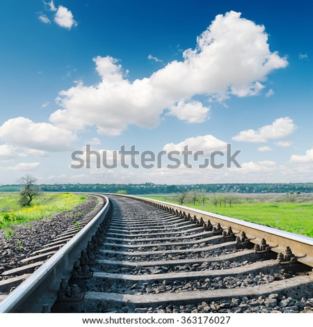 railroad closeup to horizon and white clouds in blue sky - stock photo