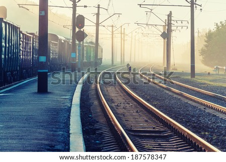 Railroad crossing and the train in the morning mist - stock photo
