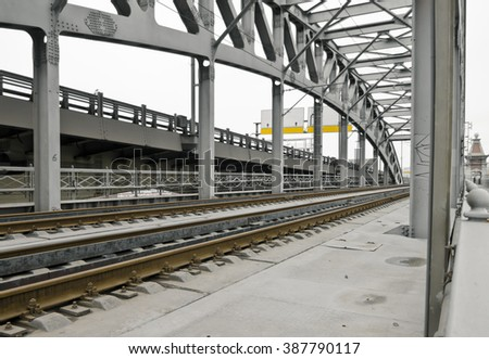 Railroad crossing on a city bridge disappearing into the distance perspective - stock photo