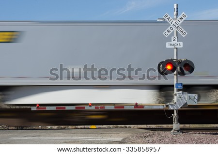 Railroad crossing sign lights and train passing. - stock photo