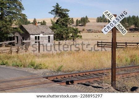 Railroad Crossing Sign Tracks Abandoned House Rural Ranch Farmland - stock photo