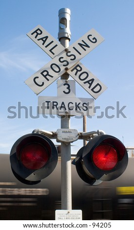 Railroad crossing sign, with train in motion. - stock photo