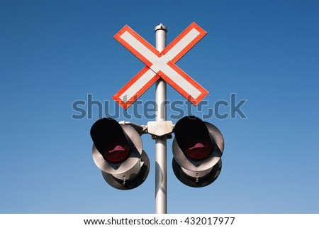 Railroad crossing signal lights and clear blue sky. - stock photo