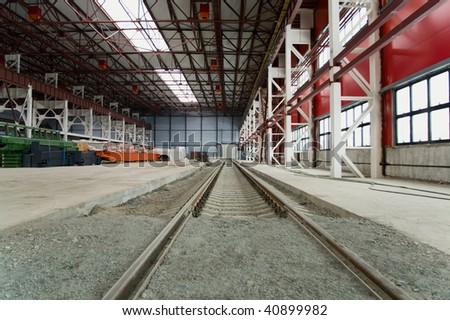 Railroad going into the distance in hangar near from hardware. Metal columns and ceiling. - stock photo