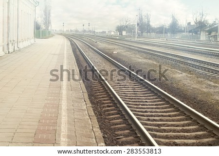 Railroad station platform in a sunny day background, cloudy sky, sun flares - stock photo