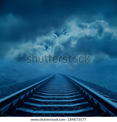 railroad to cloudy horizon in night - stock photo