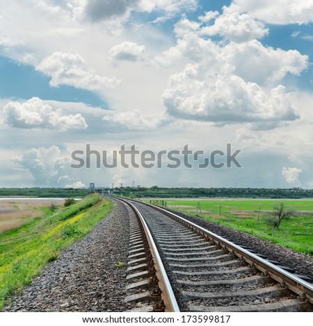 railroad to horizon and cloudy sky - stock photo