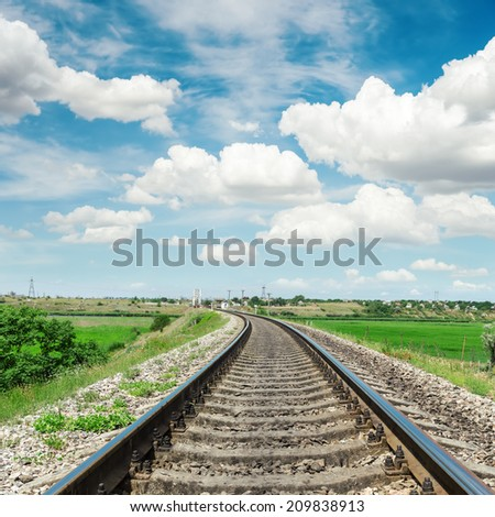 railroad to horizon in green landscape and cloudy sky - stock photo