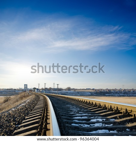 railroad to horizon under deep blue sky in sunset - stock photo