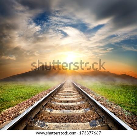 Railroad to the mountains at beautiful sunrise - stock photo