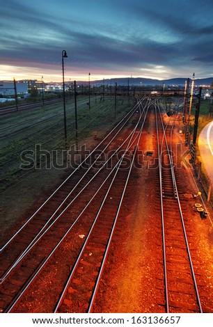 Railroad track at night with colorful sky - stock photo