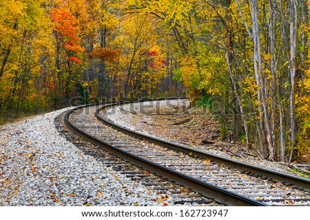 Railroad track curve around the bend and out of sight through trees with beautiful fall foliage. Shot in rural central Indiana. - stock photo