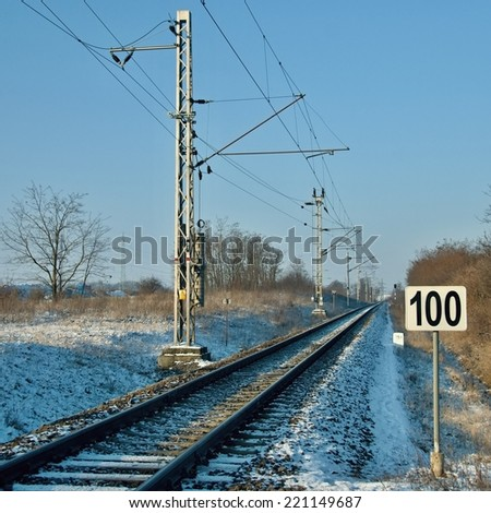Railroad track in winter country with sign of speed hundred - stock photo