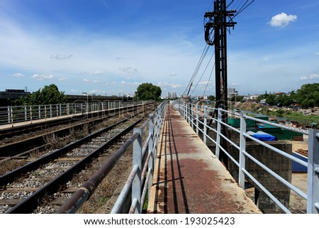 Railroad track to the city with walk path - stock photo