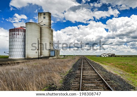 Railroad Tracks and Silos. A typical rural scene in the Palouse area of eastern Washington state with the added cloudscape on a beautiful spring day. - stock photo