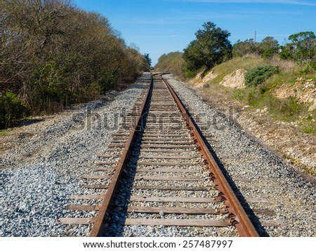 Railroad tracks appear to converge in the distance because we see them with our eyes from ground level - stock photo