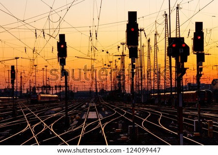 Railroad Tracks at a Major Train Station at Sunset. - stock photo