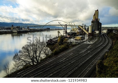 Railroad tracks by a harbor, with ship loading cargo - stock photo