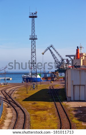 Railroad tracks by a port, with ship loading cargo. Gdynia, Poland. - stock photo