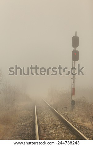 Railroad tracks in the fog and train traffic light - stock photo
