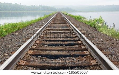 Railroad tracks lead across the lake and vanish into the fog in the woods on the far bank. - stock photo