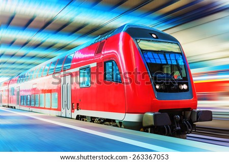 Railroad travel and railway tourism transportation industrial concept: scenic view of red modern high speed passenger commuter double decker train on tracks at the station platform with motion blur - stock photo