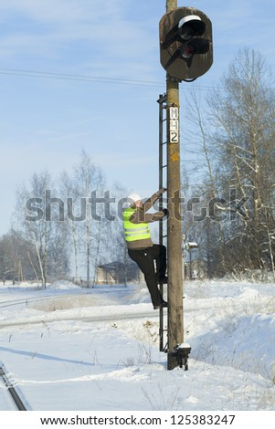 Railroad worker  climbing on  signal beacons pole - stock photo