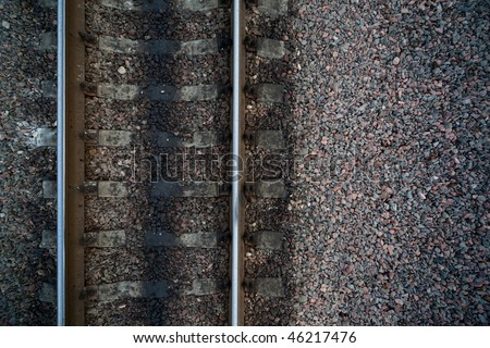 Rails and cross ties of railway among stones at left - stock photo