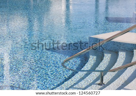 Rails and stairs leading into a blue swimmingpool - stock photo