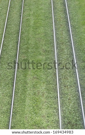 Rails on artificial grass tram, car and transportation - stock photo