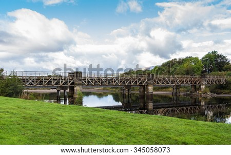 Railway beam bridge crossing River Lochy on stone piers at Old Inverlochy Castle in Fort William, Highland, Scotland, UK. The green grass banks invite to relax watching the cloudscape and blue sky. - stock photo