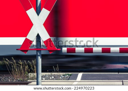 Railway crossing sign and a passing train/Railroad Crossing - stock photo